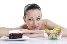 Dieting concept, beautiful young woman choosing between healthy food and tasty cakes